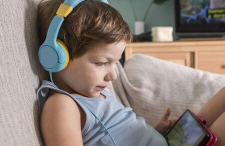 Overstimulated children concept. Too Much Screen Time. 4 years boy in headphones watching videos while tv is working.