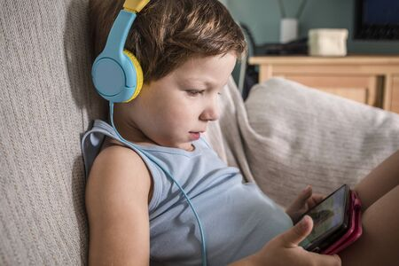 4 years boy in headphones watching videos with smartphone. Enjoying sitting on sofa in living room at home