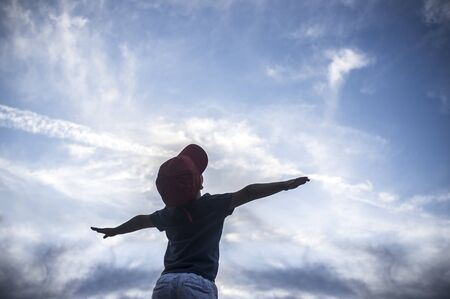 4 years old boy pretending to fly over cloudy sky. Encourage children Imagination concept 版權商用圖片