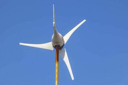 Domestic Wind Turbine mpunted over metalic pole. Blue sky background