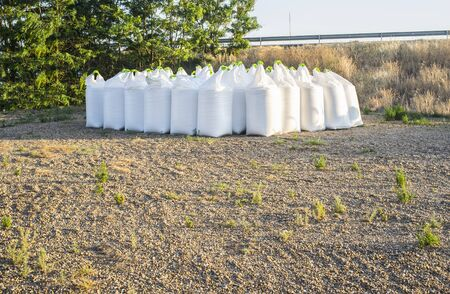 Stacks of raffia fertilizer sacks stacked over ground. Agricultural chemical fertilizer outdoors