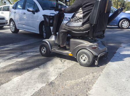 Autos, die sich an einem Fußgängerüberweg riskant dem Elektroroller nähern. Mangelnder Respekt vor dem Konzept der Mobilitätsfahrzeuge