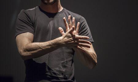 Sign language man interpreter gestures over stage during public event. Zenithal spot lighting his hands
