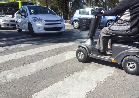 Automobiles getting close riskily to mobility scooter at pedestrian crossing. Lack of respect to mobility vehicles concept