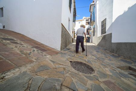 Elderly local man climbing slope narrow street of Comares, Malaga, Spain. White village up on the hill of Malaga mountains, also called Axarquia Balcony Archivio Fotografico
