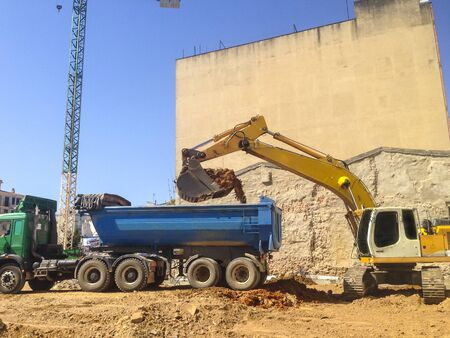 Excavator loading earth at construction site. Dump truck waiting close