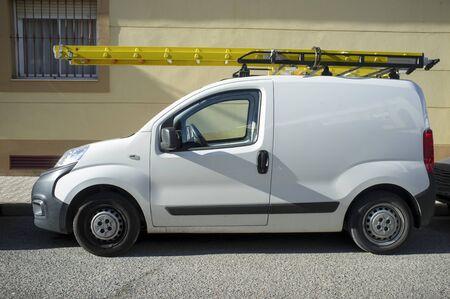 Delivery van loaded with yellow ladders. Home repair contractor van concept
