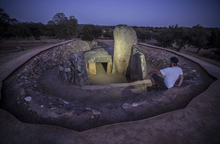 Visitor sat close Dolmen of Lacara at night. The biggest megalithic burial in Extremadura, Spain