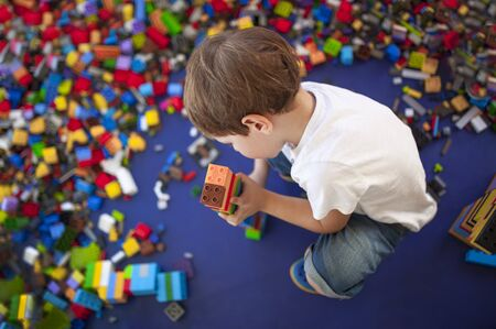 4 years boy building a tower with with interlocking plastic bricks. Selective focus