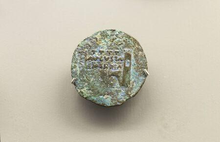 Merida, Spain - December 20th, 2017: Bronze dupondius depicting Merida Roman City Door. National Museum of Roman Art in Merida, Spain Editorial