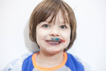 Little kid with mounth stained after eating cakes coated with synthetic food colorants. Food Coloring Safe for Kids concept