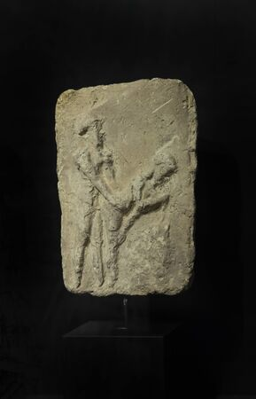 Malaga, Spain - March 2nd, 2019: Babylonian tablet representing a couple drinking beer durign act. Terracotta, 2100-1500 BC. Ifergan Collection