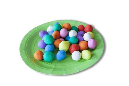 Plastic plate full of colorful playdough balls. Isolated over white background