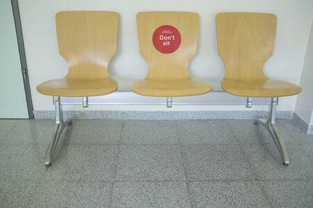 Wooden waiting chairs with social distancing sticker. Healthcare center hallway