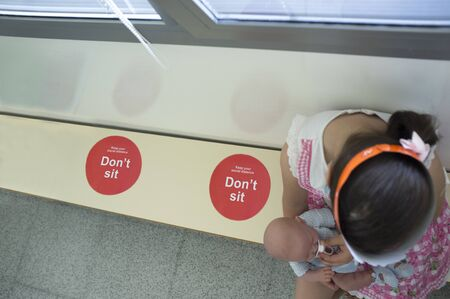 Little girl sitting on waiting bench with social distancing stickers. She holds affectionately her reborn doll