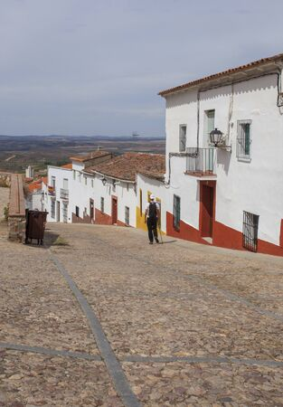 Trekker going down a steep street of Hornachos, Spain. Rural and history tourism in Extremadura Stock Photo