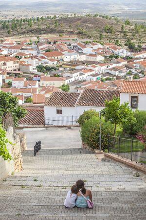Children sitting on stairs of steep street in Hornachos, Spain. Rural tourism for children in Extremadura concept