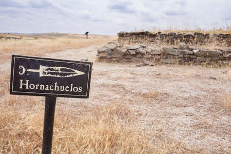 Ribera del Fresno, Spain - June 1st, 2020: Hornachuelos oppidum sign post pointing to rectangular burial mound of Necropolis. Archaeological site, Extremadura, Spain