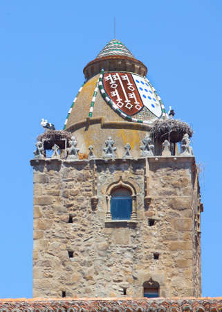 Alfiler tower, a 14th Century Gothic belfry adorned with glazed roof tiles and favorite nesting place for storks, Trujillo, Spain