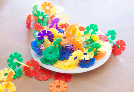 Plastic flakes blocks on plate. Instructive toy that promotes spatial hhinking and fine motor skills