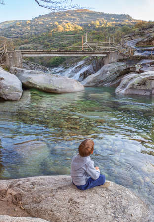 Little boy sitting at riverside of Los Pilones Gorge at Natural Reserve Garganta de los Infierno. Outstanding place for enjoying nature in Extremadura, Spain Фото со стока