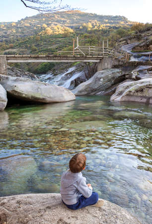 Little boy sitting at riverside of Los Pilones Gorge at Natural Reserve Garganta de los Infierno. Outstanding place for enjoying nature in Extremadura, Spain