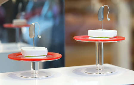Modern Hearing aid devices displayed on base. Closeup