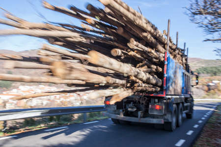 Logs truck rushes down the mountain road. Truck Car in motion blur
