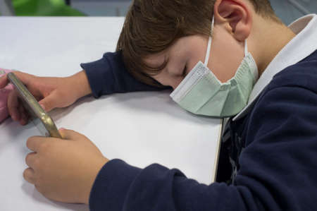 Tired 5 years old sleeping while he holds smartphone. Too much screen time concept Stock fotó