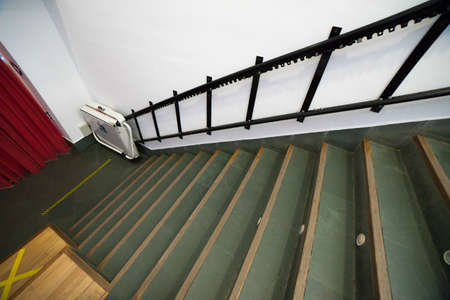 Stairlift for disabled and elderly people to climb stairs at auditorium. Theater and disability concept