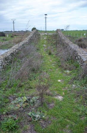 Medieval bridge of Santiago de Bencaliz near the village of Aldea del Cano, Caceres, Spain. This is part of the Via de la Plata Way or Silver Route, ancient commercial and pilgrimage path connecting Merida to Astorga