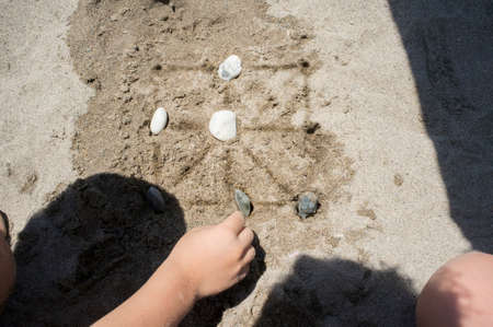 Children playing tic-tac-toe with natural board made with sand marks and beach pebbles. Overhead view