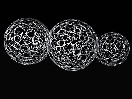 Close up of three, decorative, wire silver metal balls on a black background. Stock Photo