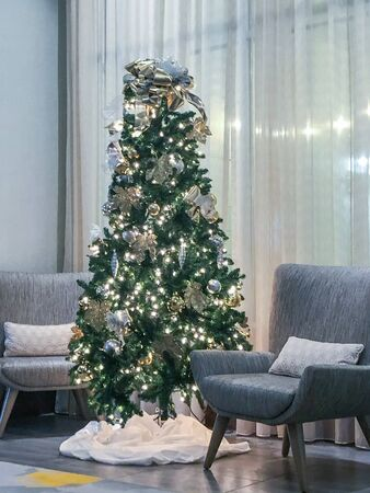 Interior shot of a Christmas tree surrounded by modern chairs in a business lobby area