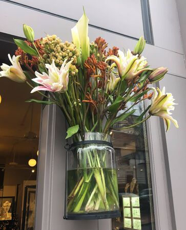 Beautiful flowers in a glass face hanging on the doorway of a shops entrance