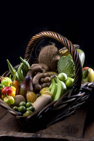 Beautiful basket with tropical fruits with black background.
