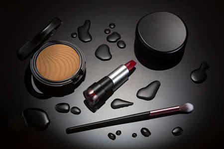 Makeup lipstick and cosmetics on black background with spot lighting.
