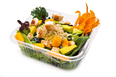 Healthy salad with grilled chicken, quinoa, mango and avocado in a takeaway plastic container.