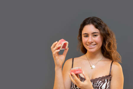 Portrait of smiling girl holding a denture with gray background.