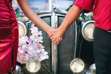 bride and groom in front of a retro car