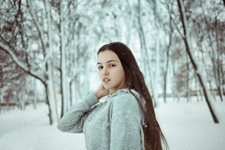 young beautiful caucasian girl in snow on background of winter park outdoors Stock Photo