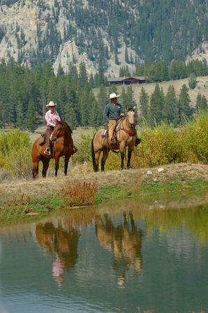 Reflection in lake of two horses with riders