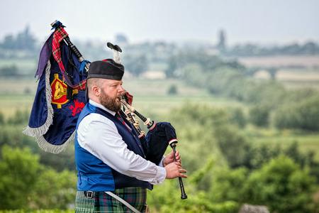 Somerset, UK - June 11, 2016: Bagpiper plays bagpipes overlooking landscape.