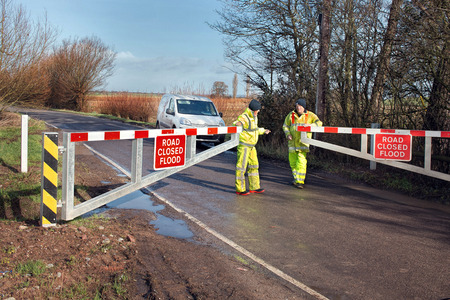 Somerset, UK - February 7, 2016: Council workers lock a road barrier, closing the road due to flooding. Editorial