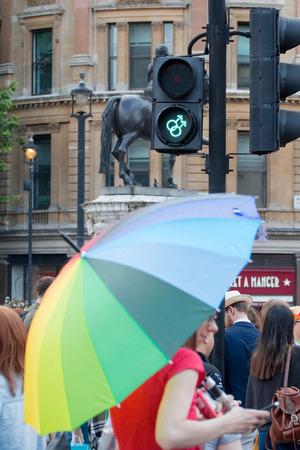 sex traffic: London, UK - June 25, 2016: LGBT Gay Pride Parade. Gay symbol pedestrian crossing and woman with rainbow unbrella