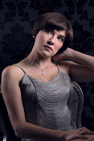 Beautiful young woman sat wearing silver vintage dress Stock Photo
