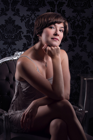 Beautiful young woman sat wearing silver vintage dress Imagens