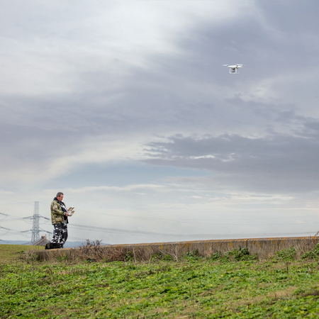 Drone pilot. Man flying drone, rural location cloudy sky.
