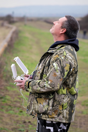 Drone pilot. Man flying drone in countryside.
