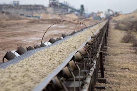 Industriële riemtransporteur die grondstoffen verplaatst.